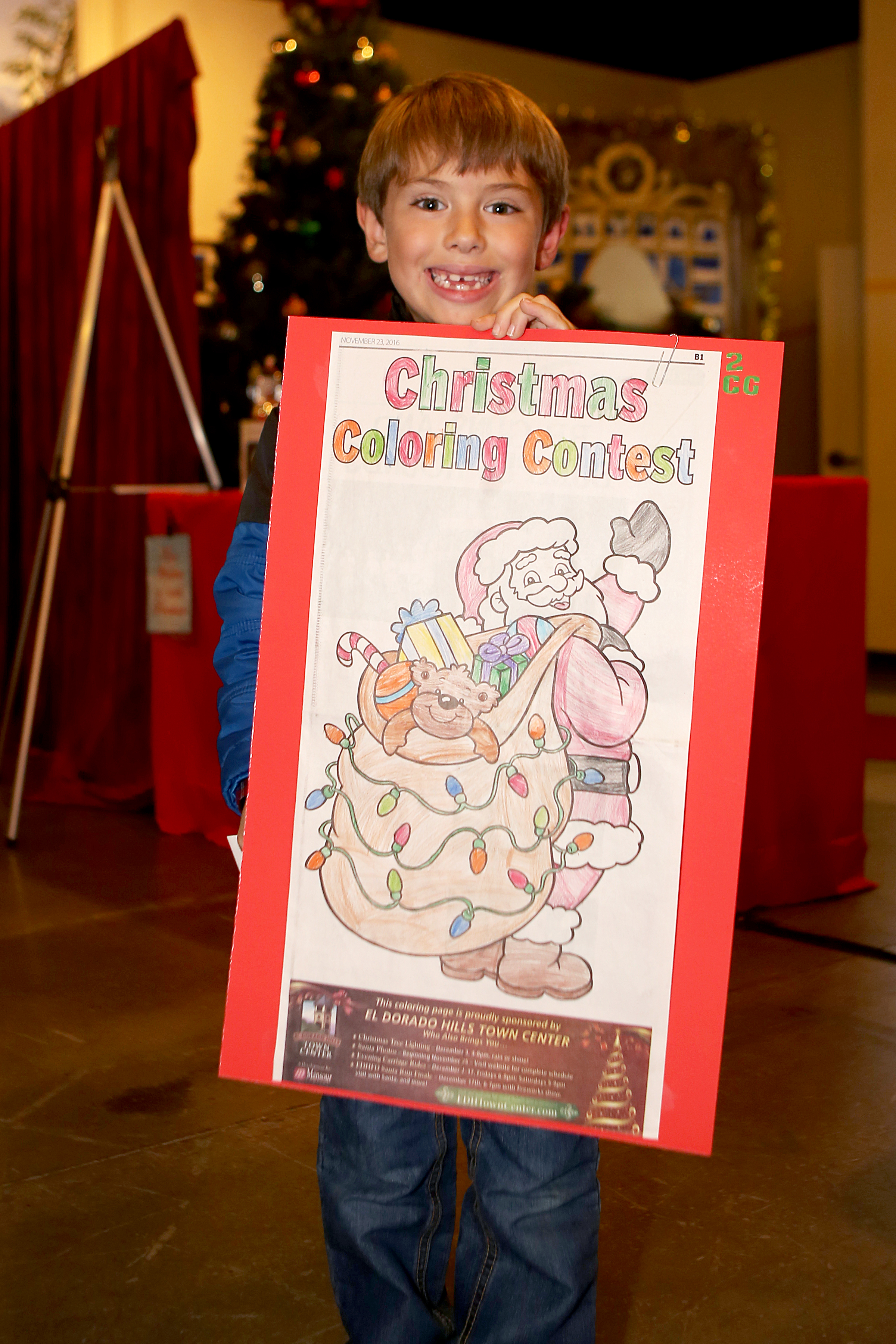 Carson Greenfield, 6, of El Dorado Hills is all smiles, holding his coloring contest entry, winning 2nd place in the coloring contest at the California Welcome Center in Town Center on Dec. 14. Democrat photo by Shelly Thorene